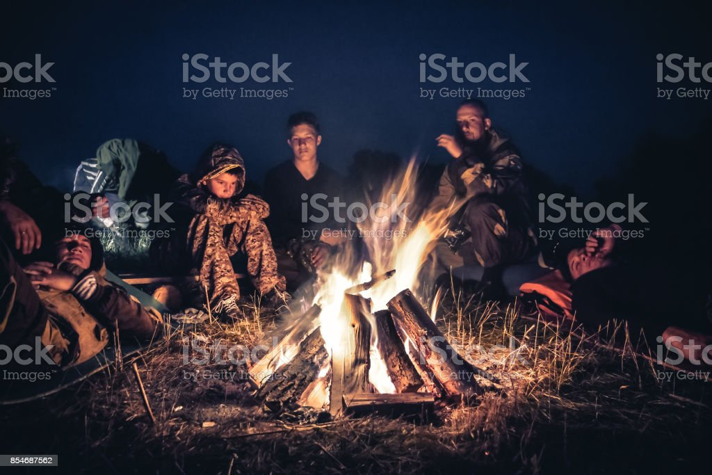 Group of people explorers resting  by the fire in outdoors camp after long hiking day in the night stock photo