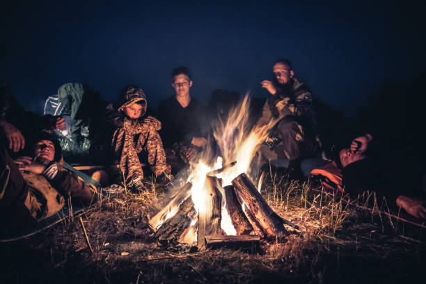 group of people explorers resting  by the fire in outdoors camp after long hiking day in the night - hunting stock photos and pictures