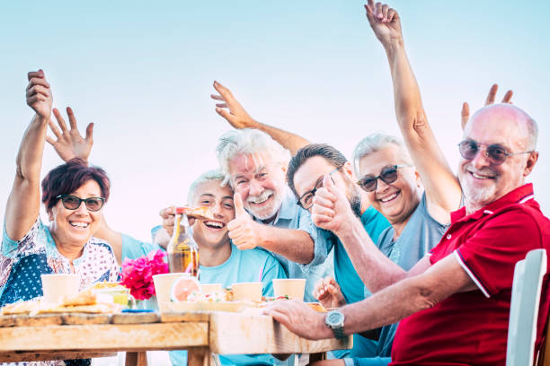 Group of people family have fun and enjoy celebration outdoor - caucasian men and women laugh around a wooden table with food and drinks - birthday with old and young stock photo