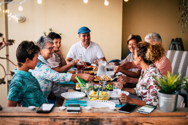 Group of people friends or family enjoy together dinner or lunch sitting at the table with food and drinks - happy people caucasian celebrate and having fun at home eating and drinking stock photo