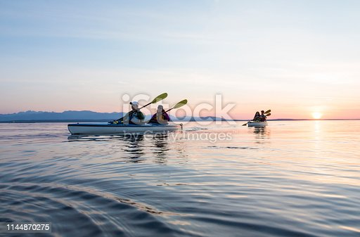 Group of people friends sea kayaking together at sunset in beautiful nature. Active outdoor adventure sports.