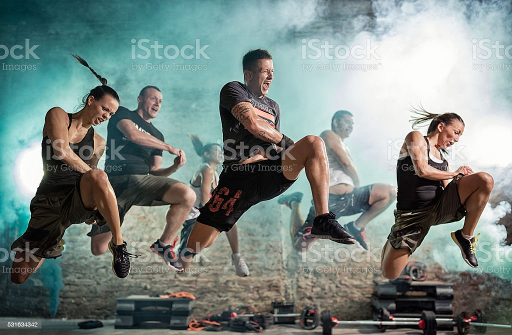 group of people full of energy doing kick exercise stock photo