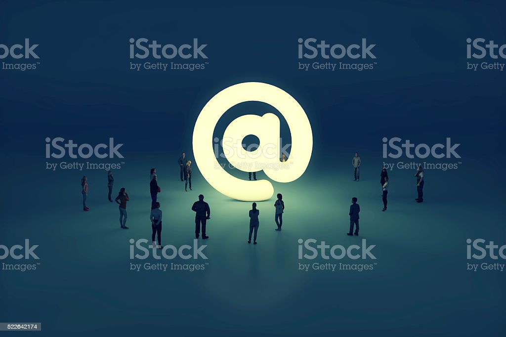 Group of people gathering around a glowing email at sign stock photo