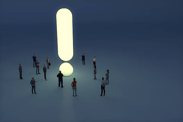 Group of people gathering around a glowing exclamation mark stock photo