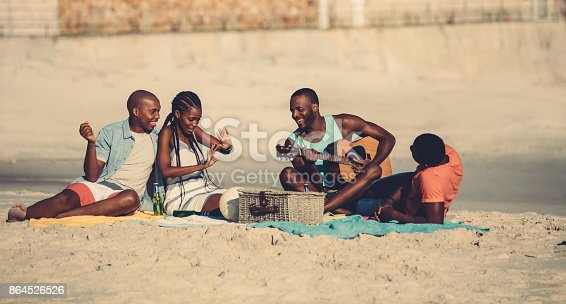 istock Group of people hanging out at the beach 864526526