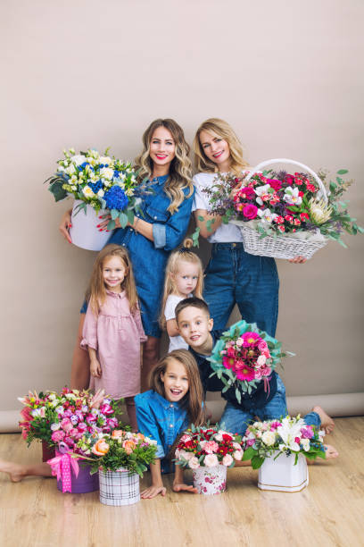 Group of people happy and beautiful, two mothers and their children holding flowers together on isolated background Group of people happy and beautiful, two mothers and their children holding flowers together on isolated background group of friends giving gifts to the birthday girl stock pictures, royalty-free photos & images