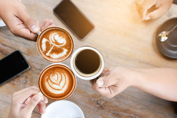 Group of people having a meeting after successful business negotiation in a coffee shop.Drinking hot beverage latte art coffee stock photo