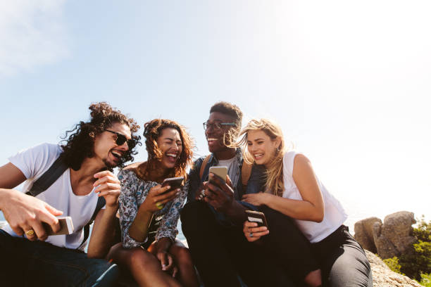 Group of people having fun on their holidays Young group of people sitting on top of mountain using smart phones and smiling. Diverse friends enjoying a day out. young adult stock pictures, royalty-free photos & images