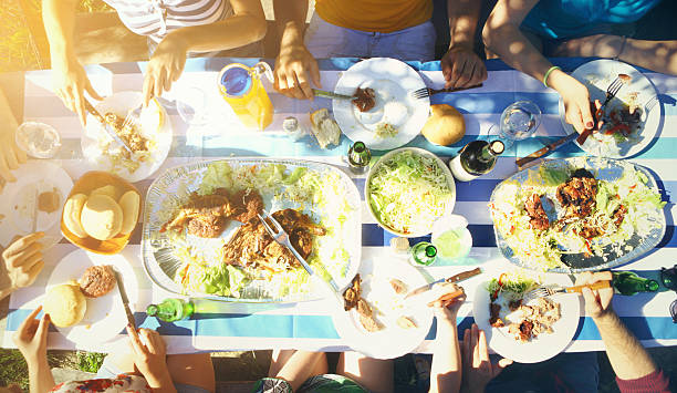 Group of people having lunch outdoors. stock photo