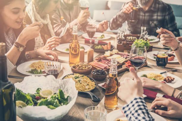 gruppe von menschen, die mahlzeit miteinander essen - bier gesund stock-fotos und bilder