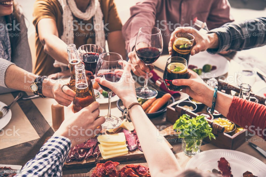 Group of people having meal togetherness dining toasting glasses stock photo