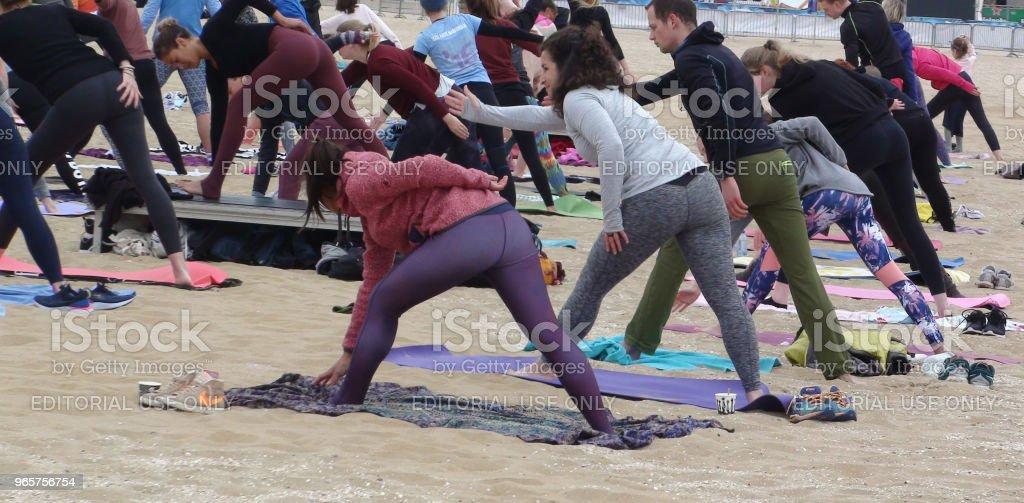 Groep van mensen die Yoga oefening op het strand - Royalty-free Buigen - Lichaamsbeweging Stockfoto