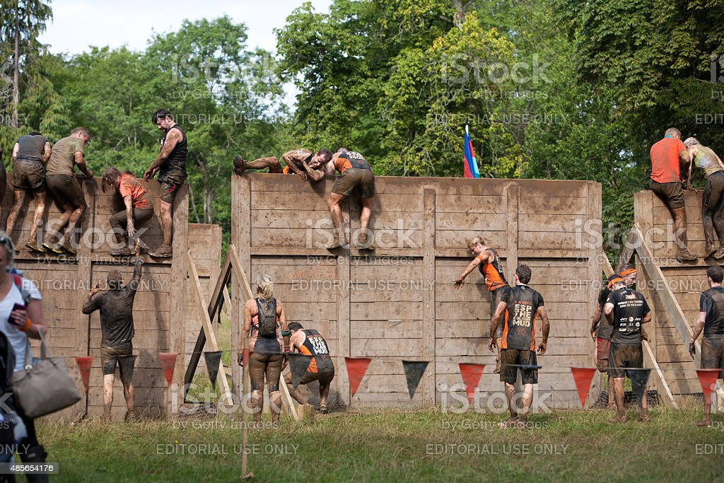 Group of people help each other over a wooden barrier stock photo