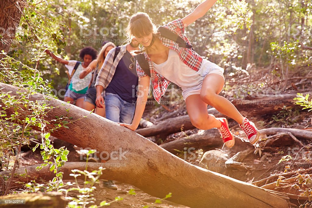 A group of people hiking and jumping over a fallen tree stock photo