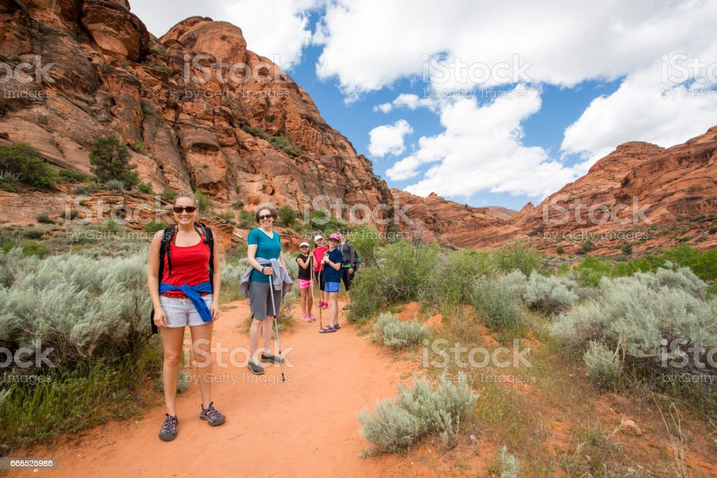 Group of people hiking in the beautiful desert cliffs in USA stock photo