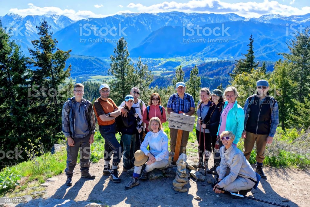 Group of people hiking on mountain top. stock photo
