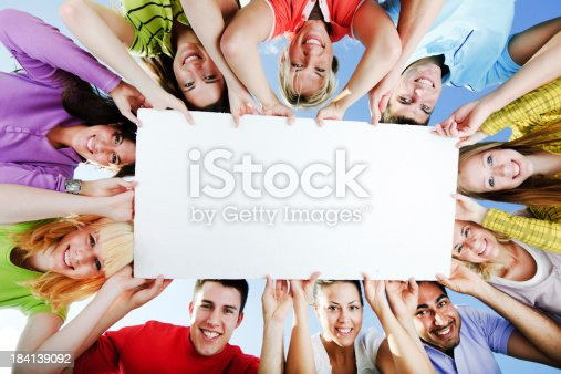 istock Group of people holding a big white board for advertisements. 184139092