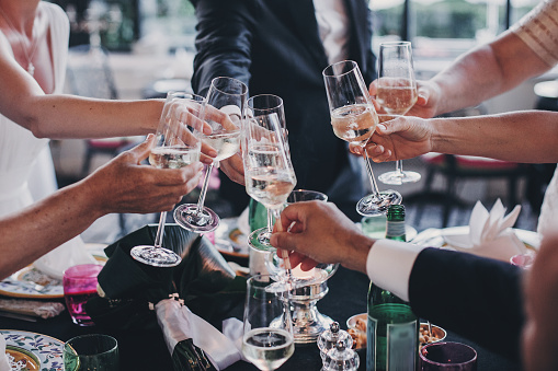 Group of people holding champagne glasses and toasting at wedding reception outdoors in the evening. Family and friends clinking glasses and cheering with alcohol at delicious feast celebration