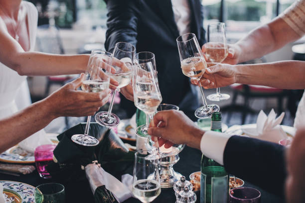 group of people holding champagne glasses and toasting at wedding reception outdoors in the evening. family and friends clinking glasses and cheering with alcohol at delicious feast celebration - group of people стоковые фото и изображения