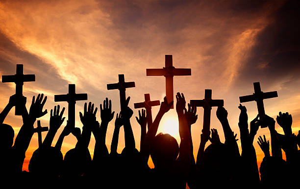 group of people holding cross and praying in back lit - praise and worship stock photos and pictures