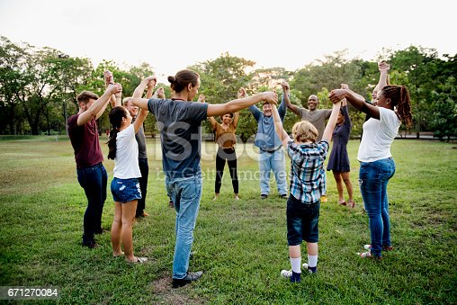 671270528istockphoto Group of people holding hand together in the park 671270084