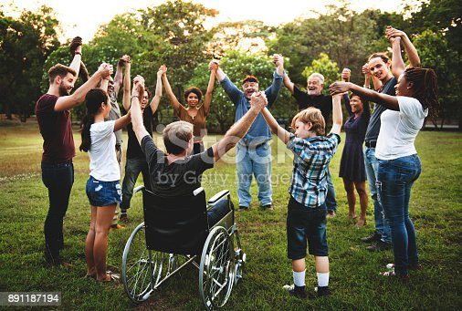 istock Group of people holding hand together in the park 891187194