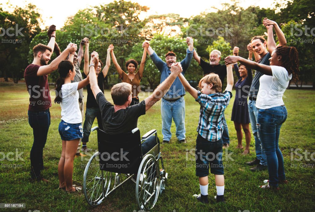 Group of people holding hand together in the park stock photo
