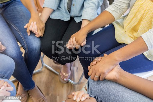 Unrecognizable group of unified people hold hands while sitting in a circle.