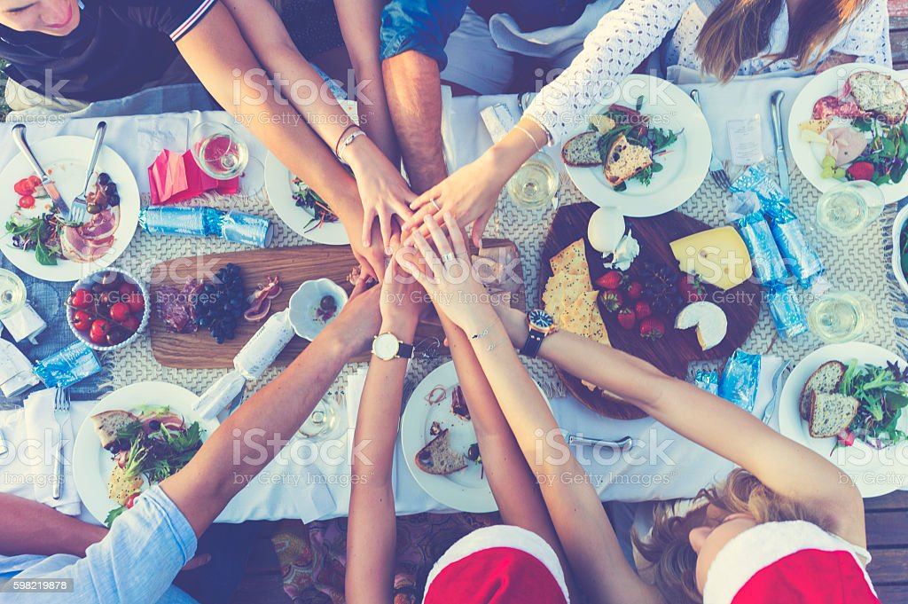 Group of people holding hands over dinner. stock photo