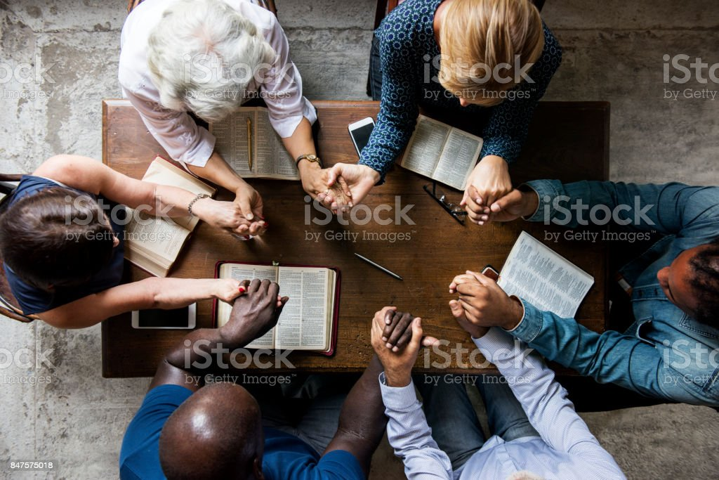 Group of people holding hands praying worship believe - foto stock