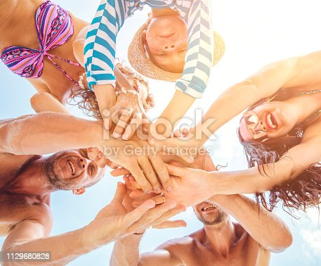 866758230istockphoto Group of people holding hands. Unity concept 1129680828