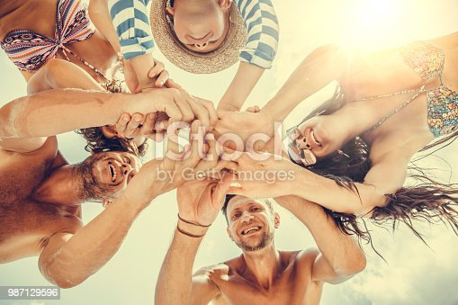 866758230istockphoto Group of people holding hands. Unity concept 987129596