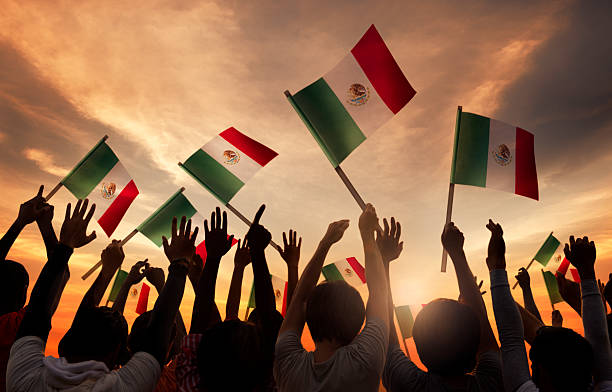 group of people holding national flags of mexico - mexico stock photos and pictures