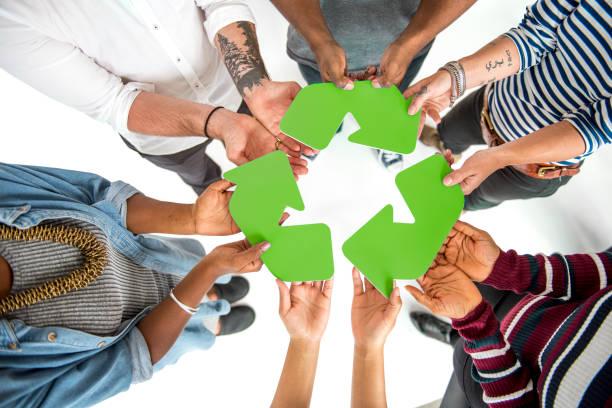 gruppe von menschen halten, recycling-zeichen-konzept - eco bastelarbeiten stock-fotos und bilder