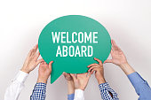 istock Group of people holding the WELCOME ABOARD written speech bubble 1003365394