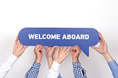 istock Group of people holding the WELCOME ABOARD written speech bubble 1007238808