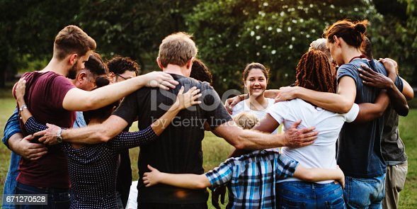 istock Group of people huddle together in the park 671270528