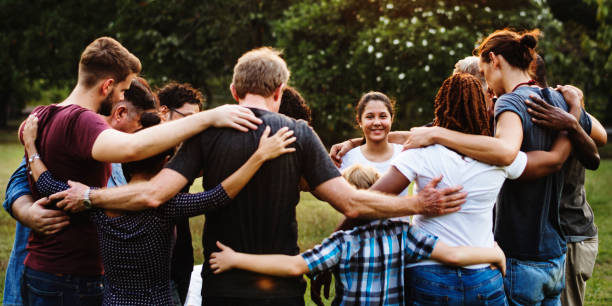 Group of people huddle together in the park stock photo