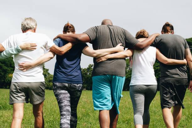 grupp människor kramas i parken - stötta beskrivande position bildbanksfoton och bilder