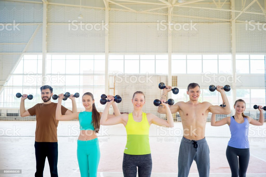 Group of people in a gym doing yoga