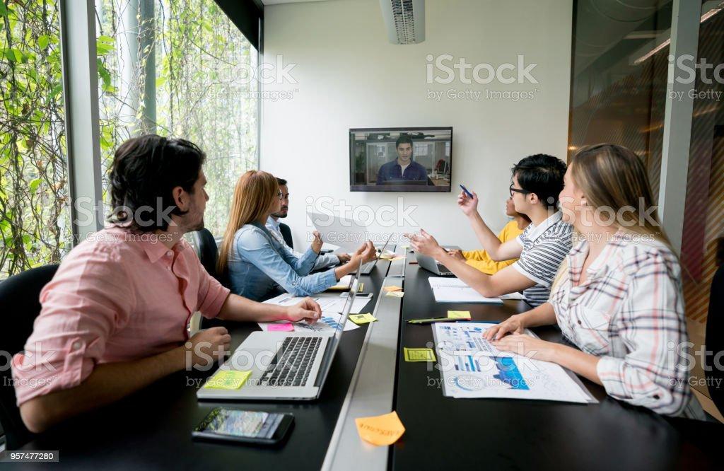 Groupe de personnes à une réunion dans un bureau créatif de faire une vidéo-conférence - Photo