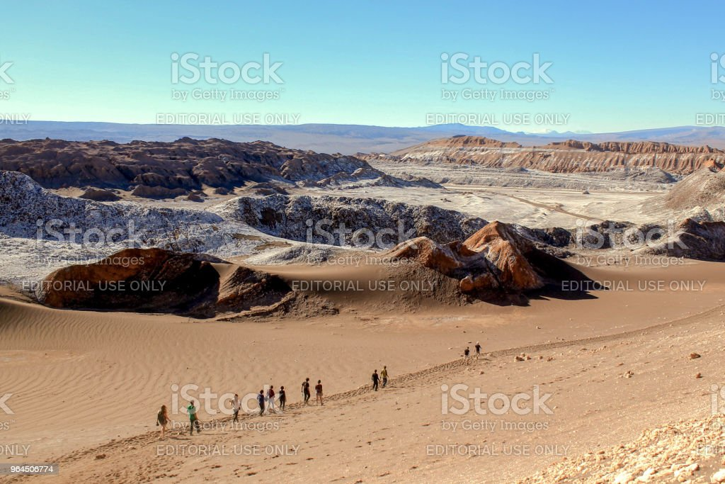 A group of people in a row descends a sandy mountain in the Atacama Desert, Chile. stock photo