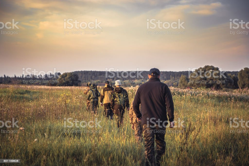Group of people in a row going away through rural field at sunset during hunting season in countryside stock photo