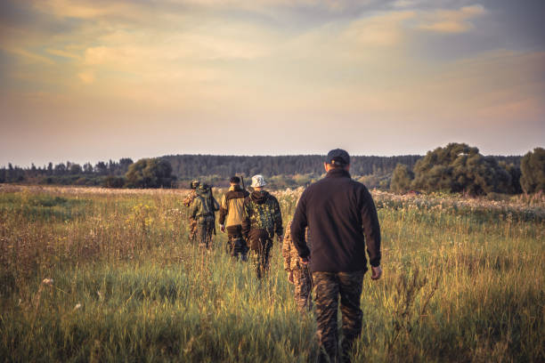 Group of people in a row going away through rural field at sunset during hunting season in countryside Group of men in a row going away through rural field at sunset during hunting season in countryside hunter stock pictures, royalty-free photos & images