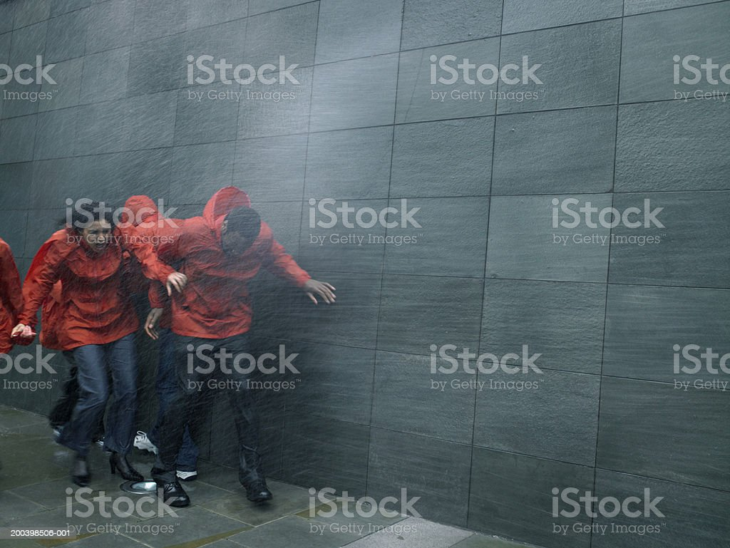 Group of people in anoraks struggling to walk against rainstorm stock photo