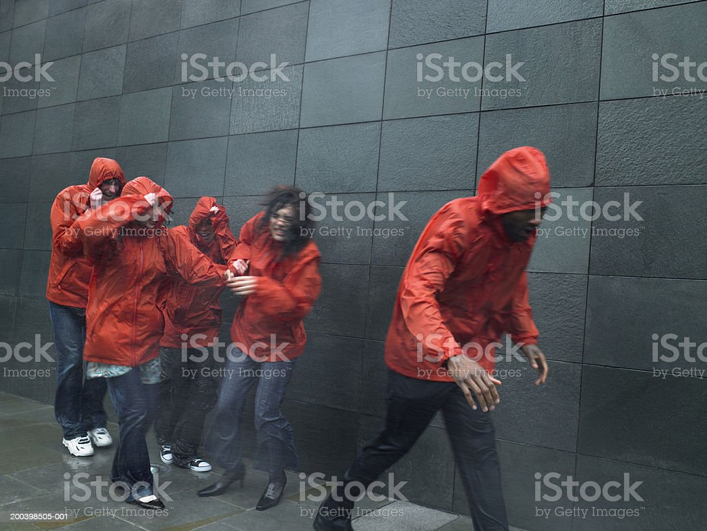 Group of people in anoraks struggling to walk against wind stock photo