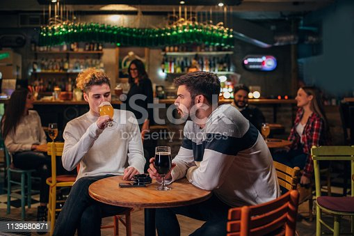 Group of people, sitting in pub drinking beer and talking.