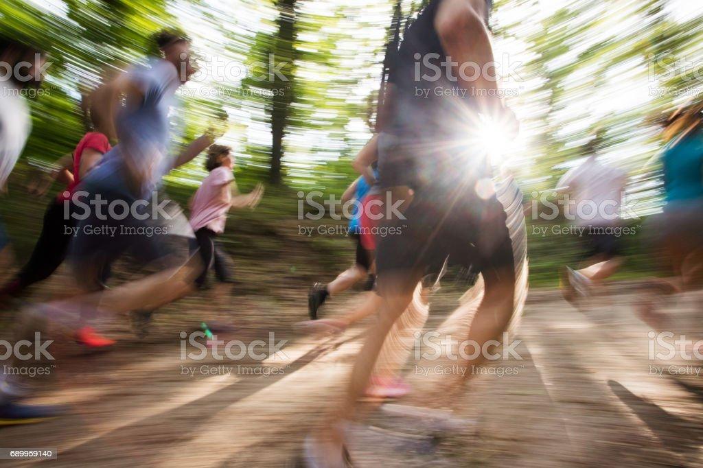 Grupo de pessoas em movimento borrado correr uma maratona na natureza. - foto de acervo