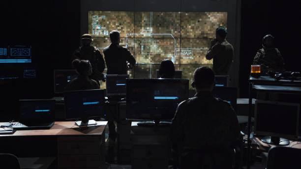 Group of people in dark room launching a missle Group of soldiers or spies in dark room with large monitors and advanced satellite communication technology launching a missle. Includes flashing yellow light. defend stock pictures, royalty-free photos & images