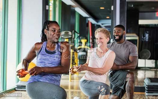 A group of three multi-ethnic people at the gym in an exercise class, doing lunges holding weights. The senior woman in the middle is in her 60s. The African-American woman is in her 50s and the man is in his 30s.